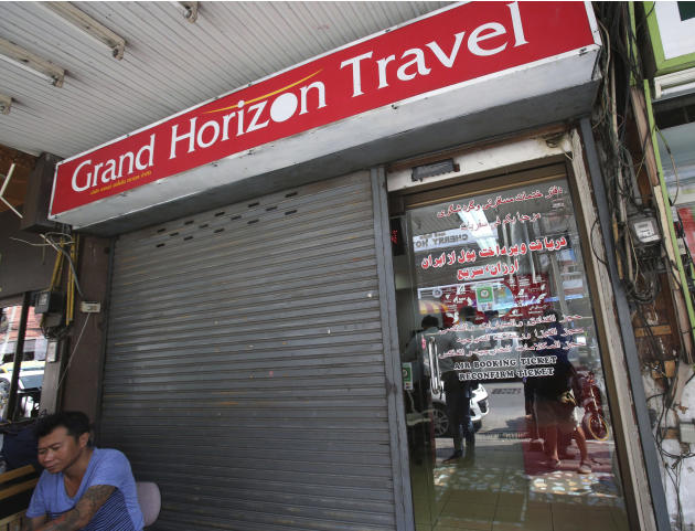 A man sits in front of closed door of the Grand Horizon Travel office in Pattaya, Chonburi province, Thailand, Monday, March 10, 2014. Thai police said owners of the travel agency told them they had r