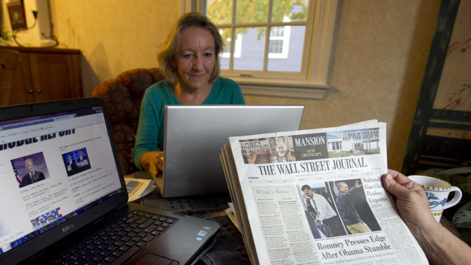 """This photo taken Oct. 5, 2012 shows independent voters Thyra and Joe Galli reading up on political news on Internet and with print newspapers at their home in Portsmouth, N.H. Thyra plans to vote for Obama and Joe is supporting Romney. New Hampshire's nickname is """"the Granite State"""" but there's nothing solid about its political landscape. Independent voters have been the reason in recent presidential elections. Today, former factory towns to the south _ Manchester and Nashua _ typically vote Republican as do the rural small towns up north, while state capital Concord and university towns like Durham, Dover, Keene and Hanover tend to lean Democratic. And the entire state is peppered with independents like Joe and Thyra Galli of Portsmouth. (AP Photo/Robert F. Bukaty)"""