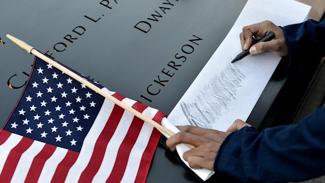 Alicia Watkins of Washington, D.C., makes a rubbing of a friend's name at the South Pool of the World Trade Center Memorial during the 11th anniversary observance of the 9/11 terrorist attacks in New York, Tuesday, Sept. 11, 2012. (AP Photo/Justin Lane, Pool)