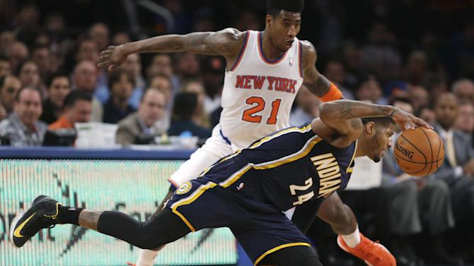 Indiana Pacers' Paul George (24) loses his balance as New York Knicks' Iman Shumpert (21) defends in the second half of Game 5 of an Eastern Conference semifinal in the NBA basketball playoffs, at Madison Square Garden in New York, Thursday, May 16, 2013. (AP Photo/Julio Cortez)