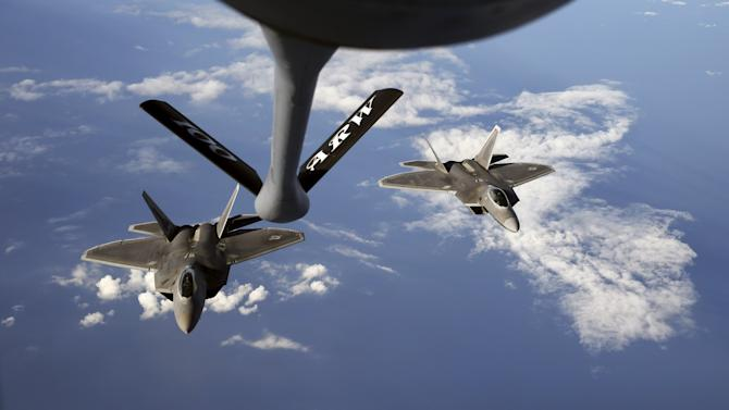 Two F-22 Raptor fighter jets approach the refuelling nozzle of a KC-135 Stratotanker over the Baltic Sea