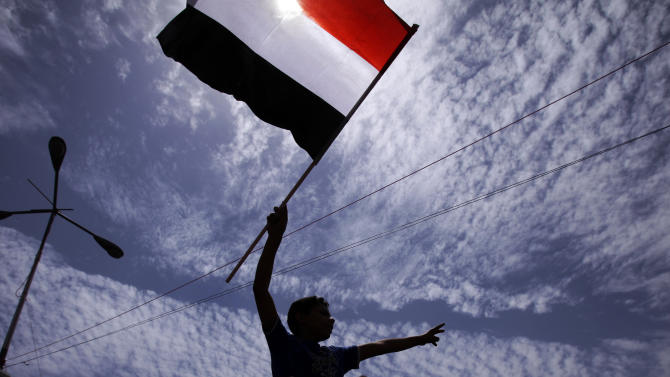 An anti-government protestor waves his flag during a demonstration demanding the resignation of Yemeni President Ali Abdullah Saleh, in Sanaa, Yemen, Monday, March 14, 2011. Yemen's president has sacked a key minister for failing to mediate with opposition parties and resolve a month long crisis that is threatening to spiral out of control. The move came as a standoff continued Monday between hundreds of policemen and plainclothes security officers and protesters camped out near Sanaa University in the capital. The protesters, who have been demanding President Ali Abdullah Saleh step down, fear they will be attacked to clear them out of the square. (AP Photo/Muhammed Muheisen)