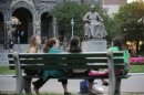 Statue of Georgetown University founder Carroll overlooks women on Georgetown campus in Washington