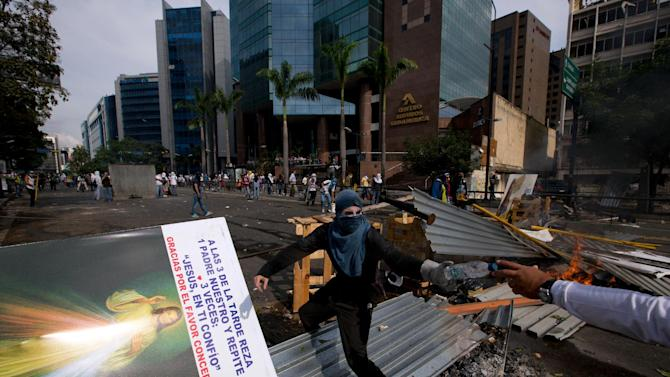 A masked anti-government demonstrator stands on a barricade during clashes with the Bolivarian National Police in Caracas, Venezuela, Tuesday, April 1, 2014. The barricades in Caracas' middle-class neighborhoods and swaths of opposition-governed cities aim to disrupt, frustrate and ultimately trigger a popular revolt by Venezuelans fed up with a tottering economy, rampant crime and crackdown on dissent. But like the broader, mostly peaceful anti-government movement it grew out of, the tactic has so far failed to sow wider unrest. (AP Photo/Fernando Llano)