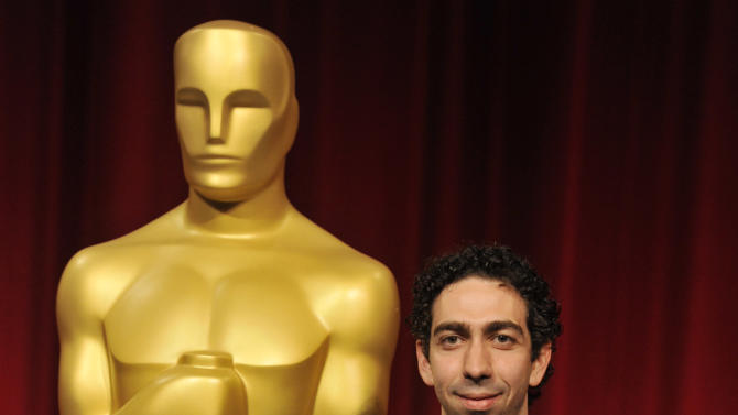 "Filmmaker Mauro Mueller of Columbia University in New York, a nominee in the Narrative Category for his film ""A World for Raul,"" poses in front of an Oscar statue before the Academy of Motion Picture Arts and Sciences 40th Student Academy Awards at the Samuel Goldwyn Theater on Saturday, June 8, 2013 in Beverly Hills, Calif. (Photo by Chris Pizzello/Invision/AP)"