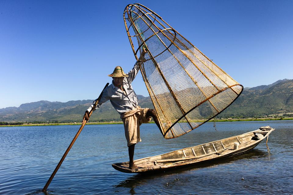 In this December 2012 photo a fisherman balances on his boat, net and oar in Inle Lake, Myanmar. (AP Photo/Richard Camp)
