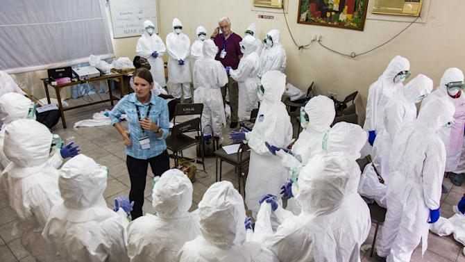 A World Health Organization, WHO, worker, left center, trains nurses to use Ebola protective gear in Freetown, Sierra Leone, Thursday,  Sept. 18, 2014. Shoppers crowded streets and markets in Sierra Leone's capital on Thursday stocking up for a three-day shutdown that authorities will hope will slow the spread of the Ebola outbreak that is accelerating across West Africa. (AP Photo/Michael Duff)