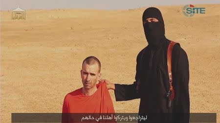 A video purportedly showing threats being made to a man Islamic State named as David Haines by a masked IS fighter in an unknown location in this still image from video released by Islamic State
