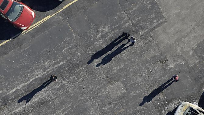In this aerial photo,people look at a row of charred cars at a used car dealership, Tuesday, Nov. 25, 2014, in Dellwood, Mo., after they were burned in overnight protests following a grand jury's decision not to indict a white police officer in the killing of unarmed black 18-year-old Michael Brown. Monday night's protests were far more destructive than any of those that followed Brown's Aug. 9 death, with more than a dozen businesses badly damaged or destroyed. (AP Photo/Charlie Riedel)