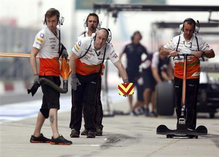 Force India team members wait for their car in the pit lane during the second practice session of the Indian F1 Grand Prix at the Buddh International Circuit in Greater Noida