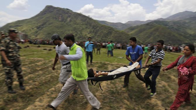 Nepalese rescuers carry an injured person to a waiting Indian air force helicopter as they evacuate victims of Saturday's earthquake from Trishuli Bazar to Kathmandu airport in Nepal, Monday, April 27, 2015. The death toll from Nepal's earthquake is expected to rise depended largely on the condition of vulnerable mountain villages that rescue workers were still struggling to reach two days after the disaster.  (AP Photo/Altaf Qadri)