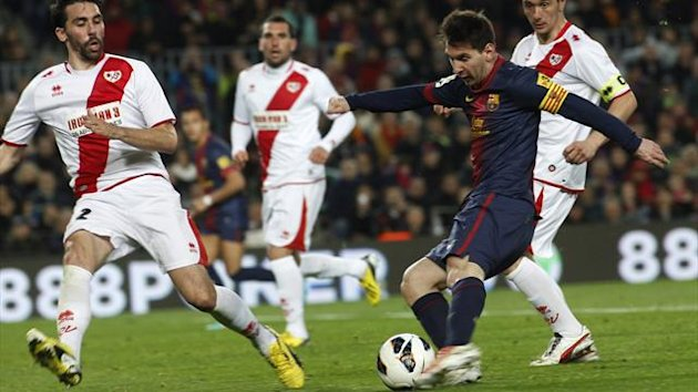 Barcelona's Lionel Messi kicks the ball surrounded by Rayo Vallecano players before scoring his second goal (Reuters)