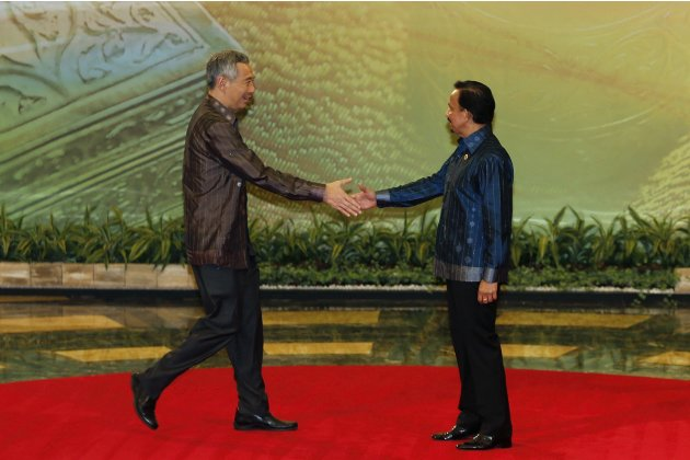 Singapore's PM Lee is greeted by Brunei's Sultan Bolkiah as Lee arrives for their working dinner during the ASEAN Summit in Bandar Seri Begawan