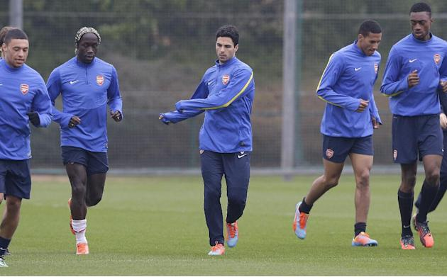 Arsenal's Mikel Arteta, centre, jogs with team mates during a training session at their London Colney training ground, Monday, March 10, 2014. Arsenal will play in a Champions League last sixteen