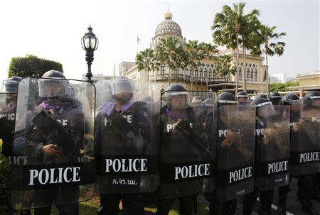 Riot policemen stand guard at the Government House during an anti-government protest in Bangkok