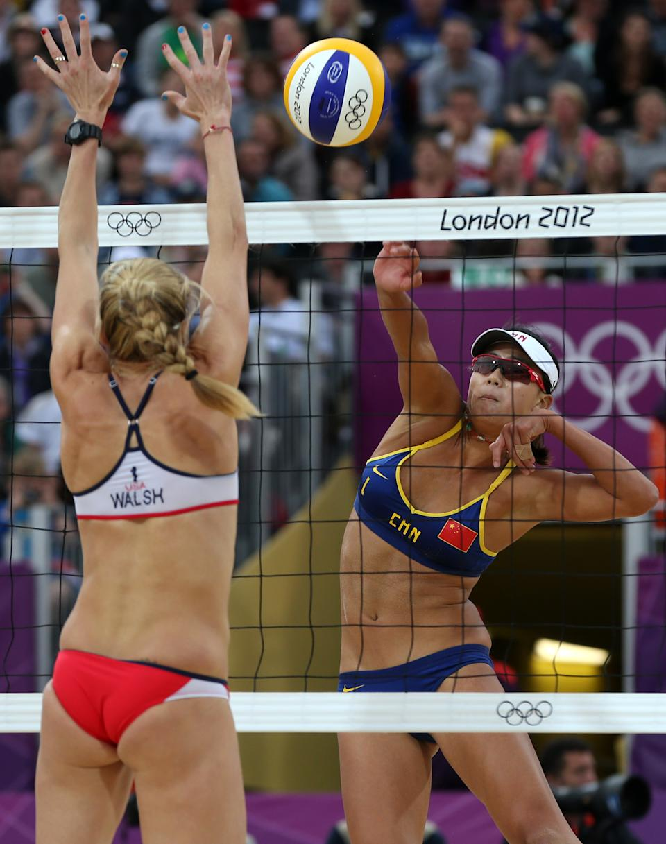China's Xue Chen, right, spikes a ball past US Kerri Walsh Jennings, left, during their semifinal women's beach volleyball match at the 2012 Summer Olympics, Tuesday, Aug. 7, 2012, in London. (AP Photo/Petr David Josek)