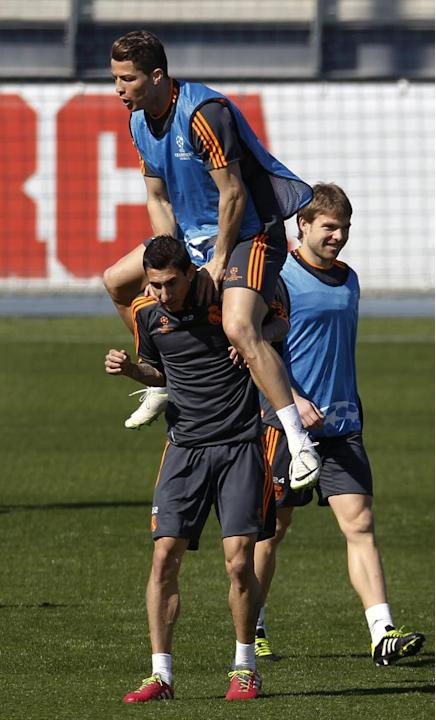 Real's Cristiano Ronaldo, left, jumps on top of Angel Di Maria from Argentina, bottom, during a training session prior to the Champions League second leg knock out soccer match between FC Schalke