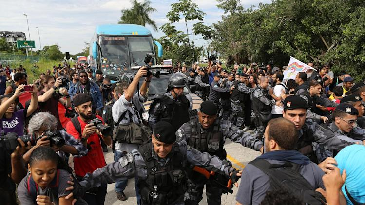 Riot police try to keep demonstrators away from the bus carrying some members of Brazil's national soccer team departing for the Granja Comary training center, where the team will stay during the World Cup, in Rio de Janeiro, Brazil, Monday, May 26, 2014. Demonstrators are protesting against the money being spent by the local government on the World Cup