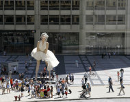 Curious spectators gather around Seward Johnson's 26-foot-tall sculpture of Marilyn Monroe, in her most famous wind-blown pose, on Michigan Ave. Friday, July 15, 2011 in Chicago. (AP Photo/Charles Rex Arbogast)