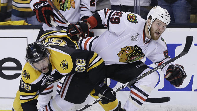 Boston Bruins right wing Jaromir Jagr (68), of the Czech Republic, ties up Chicago Blackhawks left wing Bryan Bickell (29) during the third period in Game 3 of the NHL hockey Stanley Cup Finals in Boston, Monday, June 17, 2013. The Bruins won 2-0. (AP Photo/Elise Amendola)