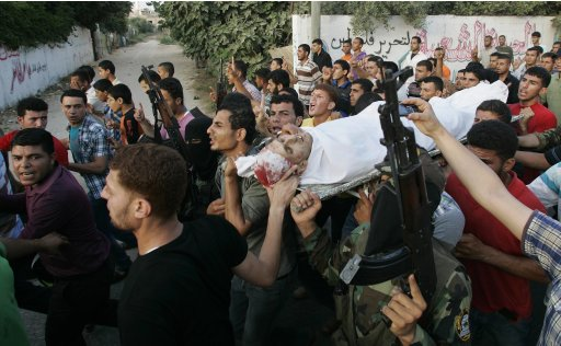 Palestinians carry the body of militant Al-Zanen during his funeral in Beit Hanoun in Gaza