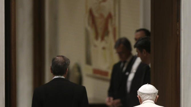 """Pope Benedict XVI leaves at the end of his weekly general audience in the Paul VI Hall at the Vatican, Wednesday Feb. 13, 2013. Looking tired but serene, Pope Benedict XVI told thousands of faithful Wednesday that he was stepping down for """"the good of the church,"""" speaking in his first public appearance since dropping the bombshell announcement of his resignation. The 85-year-old Benedict basked in more than a minute-long standing ovation when he entered the packed audience hall for his traditional Wednesday general audience. He was interrupted by applause by the thousands of people, many of whom had tears in their eyes. (AP Photo/Alessandra Tarantino)"""