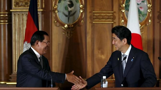 Sen shakes hands with Abe during their joint announcement after the Mekong-Japan Summit Meeting at the state guest house in Tokyo