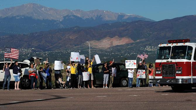 People line Old Ranch Road to cheer for the firefighters returning from a shift of fighting the Black Forest Fire Sunday morning, June 16, 2013, outside the fire camp at Pine Creek High School in Colorado Springs, Colo.  The scars of last summer's Waldo Canyon Fire can be seen in the background.  (AP Photo/The Gazette, Christian Murdock) MAGS OUT