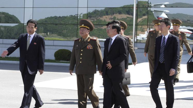 High-ranking North Korean party and military official Choe Ryong Hae, second left, prepares to depart for China as a special envoy of North Korean leader Kim Jong Un, at Pyongyang airport, North Korea Wednesday, May 22, 2013. The trip by Choe, a vice marshal who is director of the General Political Bureau of the Korean People's Army, is the highest-profile visit by a North Korean official to neighboring China this year and takes place at as Beijing is under pressure to rein in Pyongyang's provocations. (AP Photo/ Kim Kwang Hyon)