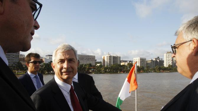 President of the French National Assembly Claude Bartolone (C) stands in a boat during a visit on the Ebrie lagoon in Abidjan