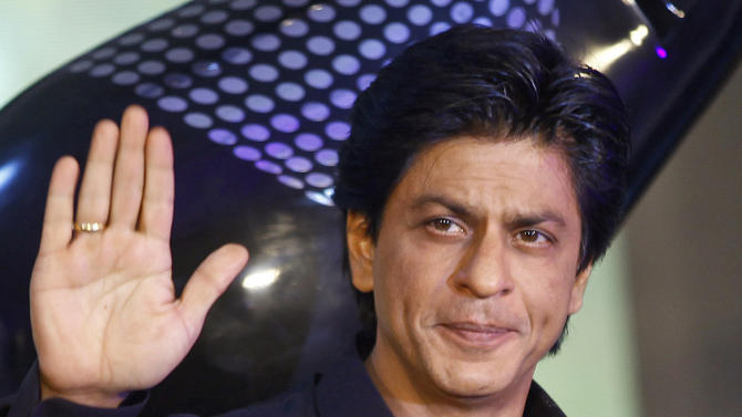 FILE- In this Jan. 29, 2013 file photo, Bollywood actor Shah Rukh Khan waves as he holds a trophy during the unveiling of TOIFA Bollywood awards in Mumbai, India. Khan is denying he knew the gender of his son before the boy's premature birth. Prenatal gender testing is illegal in India to prevent sex-selective abortions.(AP Photo/Rafiq Maqbool, file)