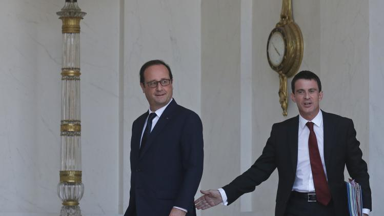 French President Hollande and Prime Minister Valls leave after the weekly cabinet meeting at the Elysee Palace in Paris