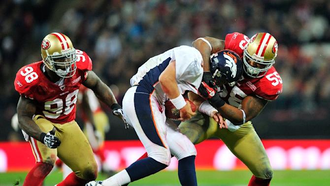 Ahmad Brooks of the San Francisco 49ers (R) tackles Kyle Orton of the Denver Broncos (C) during their NFL International series game at Wembley Stadium in London on October 31, 2010