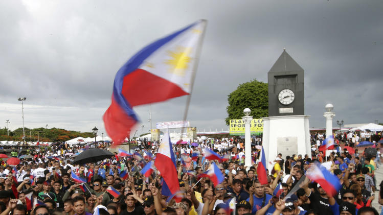 Filipinos wave Philippine flags following flag raising rites to celebrate the 116th anniversary of Philippine independence Thursday, June 12, 2014, in Manila, Philippines. Vice President Jejomar Binay and former president and now Manila Mayor Joseph Estrada led the celebration in Manila in lieu of President Benigno Aquino III, who led the flag-raising rites in central Philippines. The Philippine revolutionaries declared independence from Spain in 1898. (AP Photo/Bullit Marquez)
