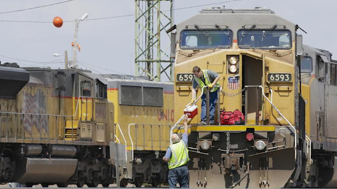 In this photo from June 6, 2014, train operators remove their belongings from a Union Pacific locomotive at a rail yard in Council Bluffs, Iowa. When American freight trains delivered cargo after World War II, the steam-belching beasts commonly had seven people aboard _ an engineer, a conductor, up to four brakemen and a fireman. Since then trains have grown longer, crews were reduced to two and now railroads want to put a single person in charge, an engineer.  (AP Photo/Nati Harnik)