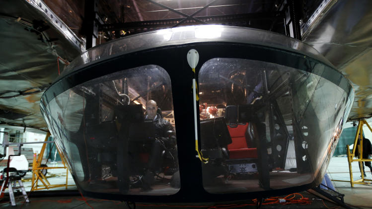 Aerospace engineer Munir Jojo works in the cockpit of the Aeroscraft airship, a high-tech prototype airship, in a World War II-era hangar in Tustin, Calif., Thursday, Jan. 24, 2013. Work is almost done on a 230-foot rigid airship inside a blimp hangar at a former military base in Orange Co. The huge cargo-carrying airship is has shiny aluminum skin and a rigid, 230-foot aluminum and carbon fiber skeleton. (AP Photo/Jae C. Hong)