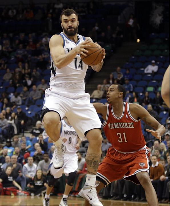 Minnesota Timberwolves' Nikola Pekovic, left, of Montenegro, jumps to intercept a pass as Milwaukee Bucks' John Henson, right, signals a teammate in the first quarter of an NBA basketball game