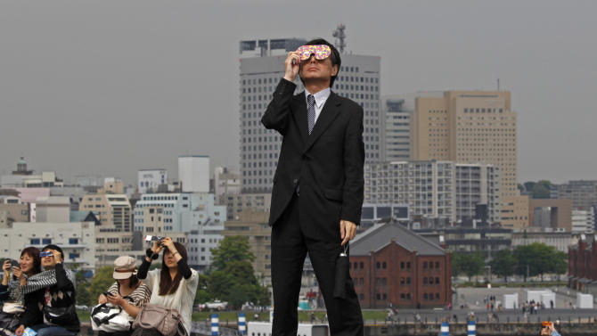 """A business man watches an annular solar eclipse at a waterfront park in Yokohama, near Tokyo, Monday, May 21, 2012.  Millions of Asians watched as a rare """"ring of fire"""" eclipse crossed their skies early Monday.  The annular eclipse, in which the moon passes in front of the sun leaving only a golden ring around its edges, was visible to wide areas across the continent. (AP Photo/Shuji Kajiyama)"""