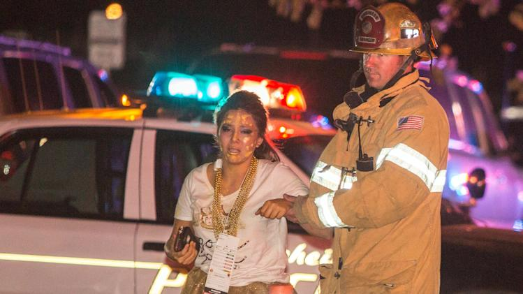 A firefighter assists an injured student after a stage collapsed during a student event at Servite High School in Anaheim, Calif., Saturday, March 8, 2014. Authorities said 30-40 people were taken to hospitals with mainly minor injuries. (AP Photo/Kevin Warn)