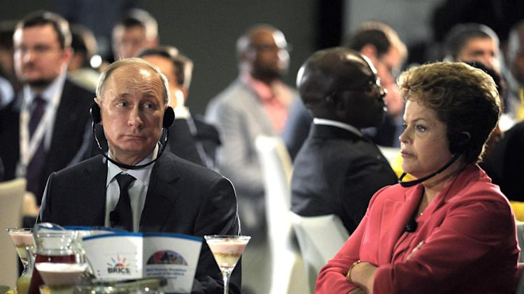 In this photo taken on Tuesday, March 26, 2013, Russian President Vladimir Putin, left, and Brazilian President Dilma Rousseff listen to an orator during their meeting in Durban, South Africa. Vladimir Putin is on a working visit and set to attend a meeting with the leaders of Brazil, Russia, India and China (BRICS) during an Africa Dialogue Forum in Durban on Wednesday. (AP Photo/RIA-Novosti, Alexei Druzhinin, Presidential  Press Service)