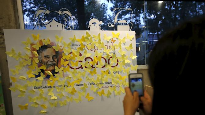 A fan takes pictures with her cellphone at yellow papers butterfly cutout with messages on a banner with an image of Nobel Prize-winning novelist Gabriel Garcia Marquez, on the first anniversary of his death, at a bookstore in Mexico City
