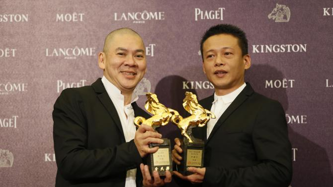 """Best director Tsai Ming Liang, left, and Best Leading Actor Lee Kang Sheng, hold their awards for their film """" Stray Dogs """" at the 50th Golden Horse Awards in Taipei, Taiwan, Saturday, Nov. 23, 2013. The Golden Horse Awards is the Chinese-language film industry's biggest annual events. (AP Photo/Wally Santana)"""