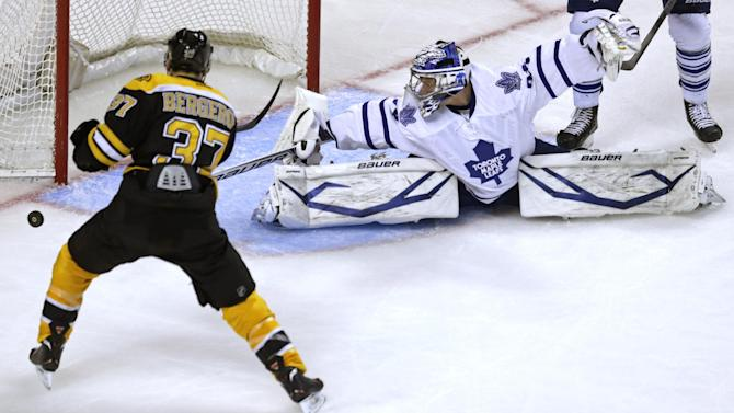 Toronto Maple Leafs goalie James Reimer, right, spreads to make a save on a shot by Boston Bruins center Patrice Bergeron (37) during the second period in Game 5 of an NHL hockey Stanley Cup playoff series, in Boston on Friday, May 10, 2013. (AP Photo/Charles Krupa)