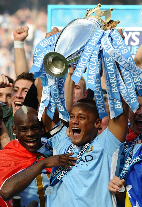 Manchester City's Belgian Captain Vincent Kompany Lifts The Premier League Trophy, And Celebrates With Italian Striker AFP/Getty Images