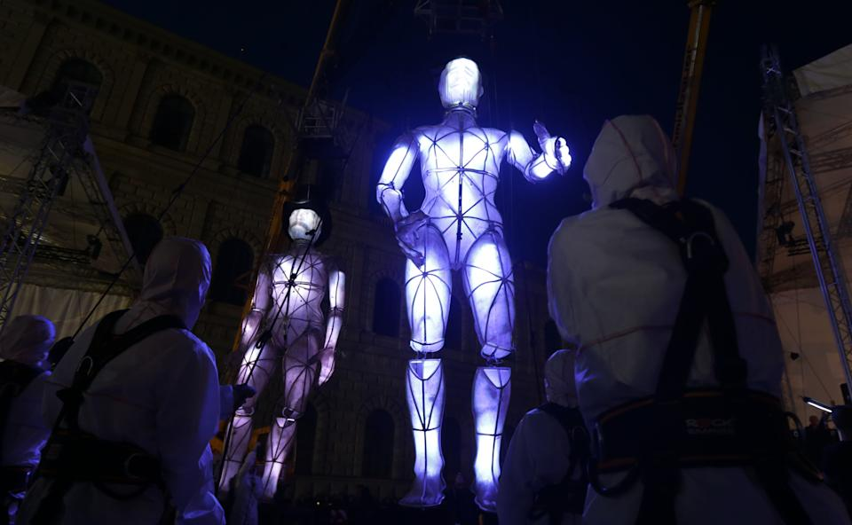 Actors perform with giant illuminated puppets during an open air event in front of the Munich opera, southern Germany, on Friday, June 28, 2013. Munich celebrates the 200. birthday of composers Richard Wagner and Guiseppe Verdi. (AP Photo/Matthias Schrader)