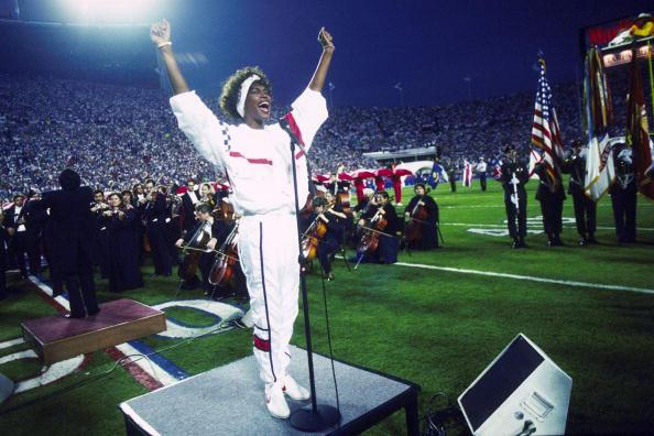 Whitney Houston sings the National Anthem during the pregame show at Super Bowl XXV while tens of thousands of football fans wave tiny American flags in an incredible outburst of patriotism during the