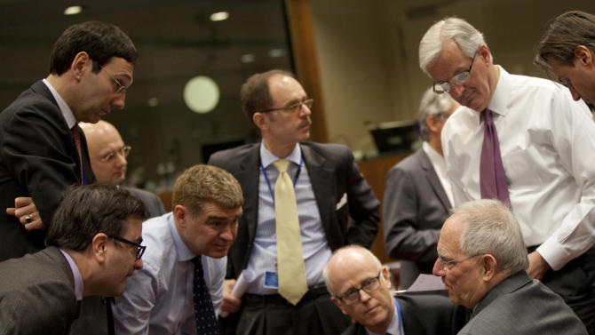 German Finance Minister Wolfgang Schaeuble, bottom right, speaks with European Commissioner for Internal Market Michel Barnier, second right, and members of various delegations during a meeting of  EU finance ministers in Brussels on Tuesday, March 5, 2013. European Union finance ministers were expected Tuesday to give wide political approval to capping bankers' bonuses, with Britain being the only country of the 27-nation bloc staunchly opposing the measure, diplomats said.  (AP Photo/Virginia Mayo)