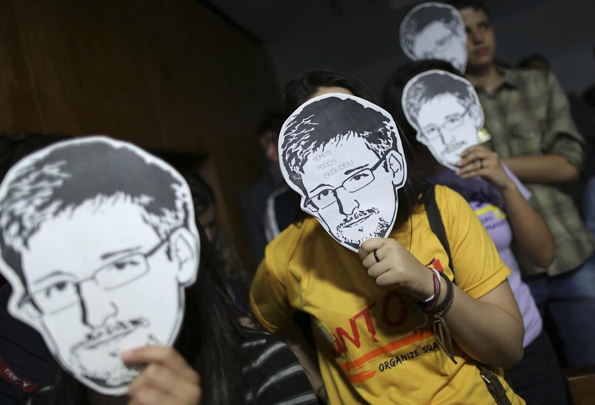 People hold Snowden masks in Brasilia