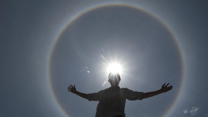 A man poses for photos as solar halo is seen in the sky of Brasilia