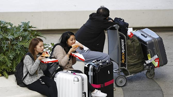 Travelers eat pizza outside Tom Bradley International Terminal at Los Angeles Airport in Los Angeles, California